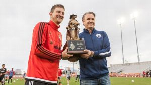 Rene Van de Zande give the Armadillo trophy to Bobby Boswell (DC United)
